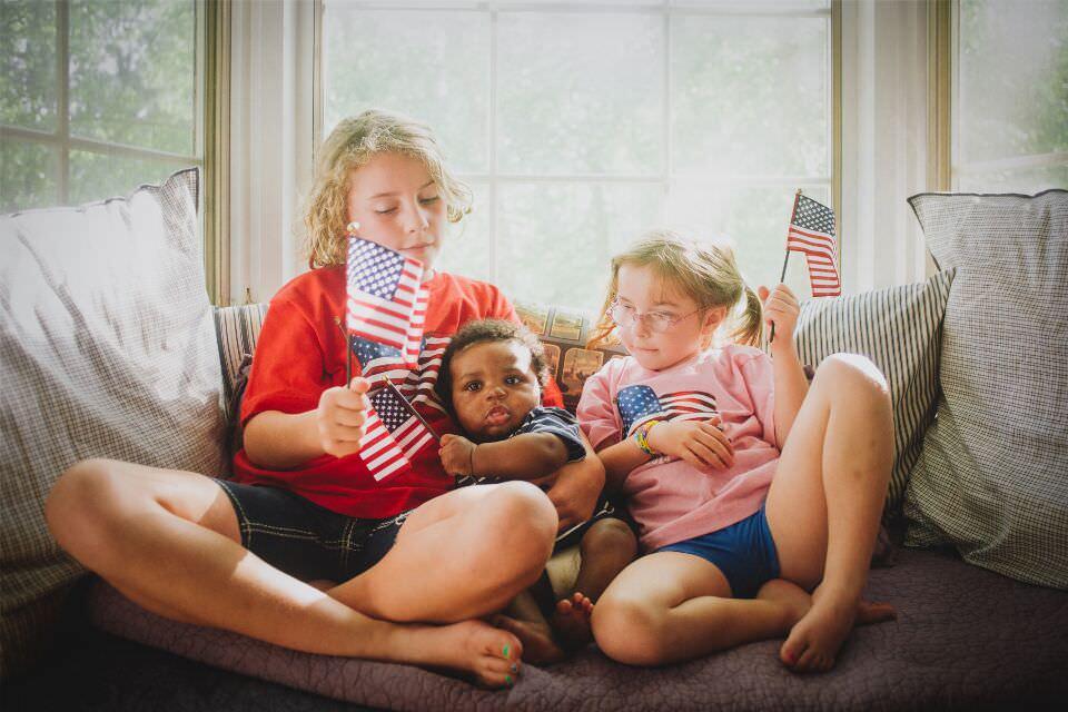 Drei Kinder mit amerikanischen Flaggen in der Hand.