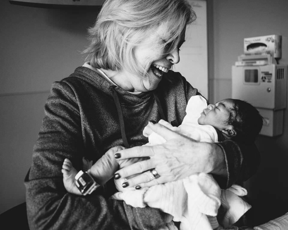 Eine Frau lacht herzlich und hält ein Baby auf dem Arm.