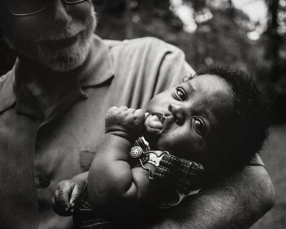 Ein Baby auf dem Arm seiner Großvaters.