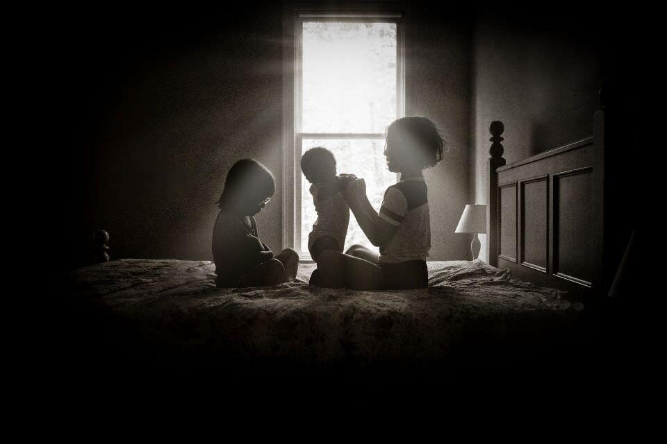 Zwei Mädchen spielen mit einem Baby auf einem Bett.