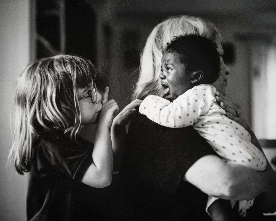 Ein schreinendes Baby auf dem Arm einer Frau.