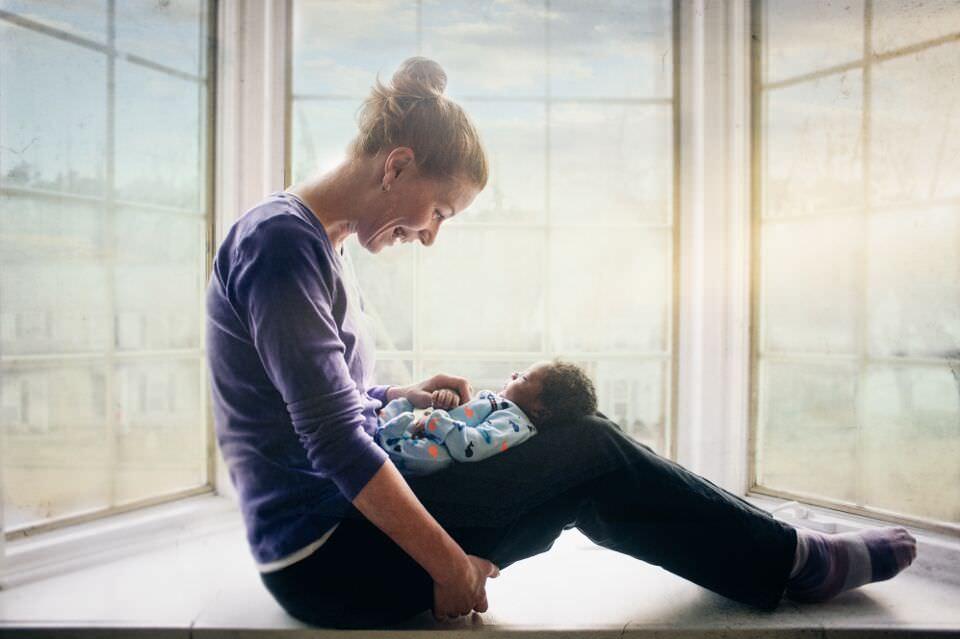Eine Mutter sitzt im Fenster und schaut ihr Kind an.