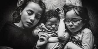 Drei Kinder schlafen nebenainander und aneinander gekuschelt.