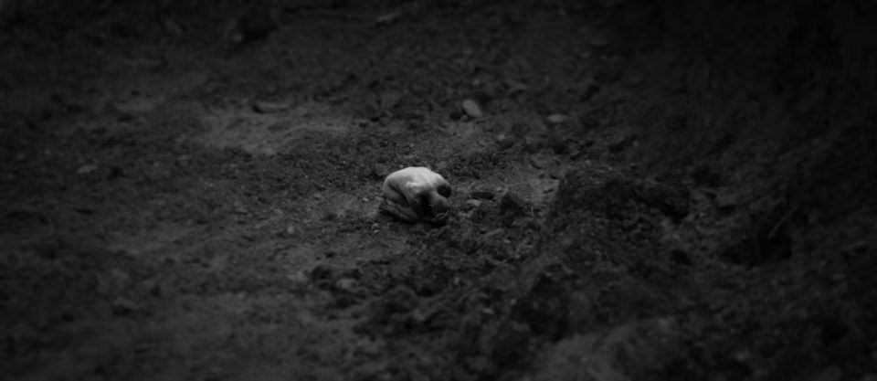 Eine zusammengerollte, nackte Person auf einer dunklen, kargen Erdfläche.