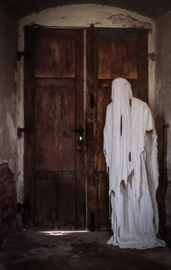 Ein Geist aus Gips steht vor einer hölzernen Tür
