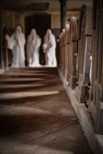 Kirchgang mit drei unscharfen Geistern im Hintergrund