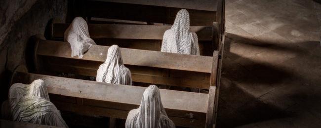 Geister sitzen auf einer Kirchbank. Von oben fotografiert.