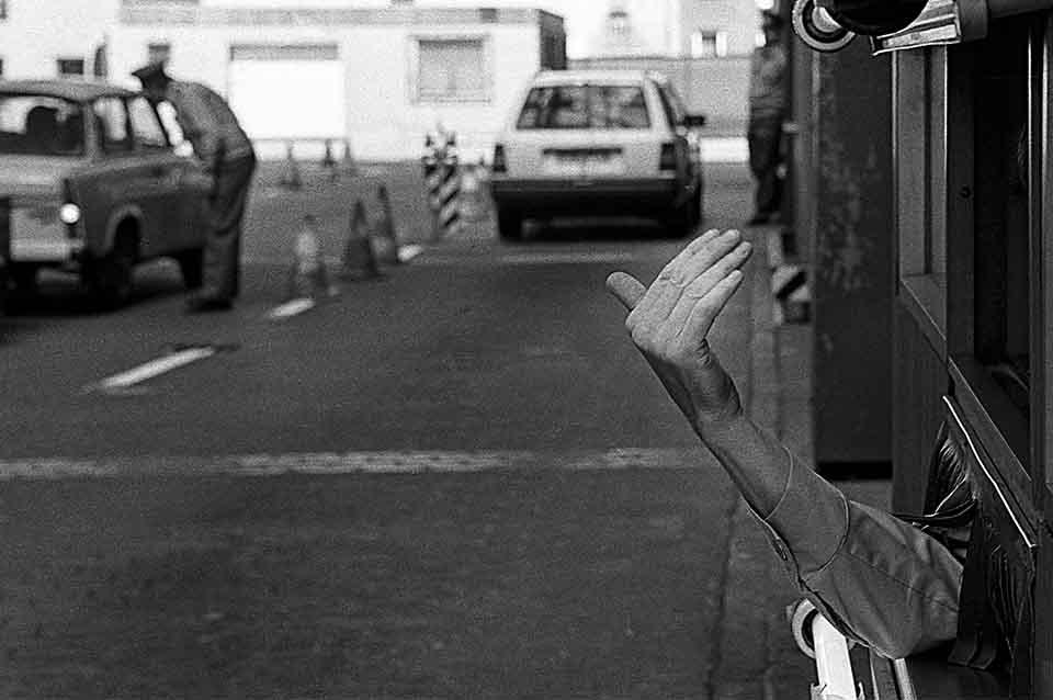 Die Hand eines Grenzkontrolleurs winkt zur Durchfahrt auf der Ostberliner Seite des Grenzübergangs Checkpoint Charlie.
