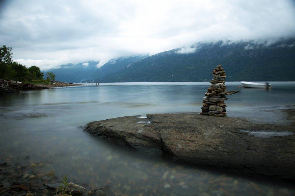Ein Turm aufgestapelter Steine am Ufer eines Sees.