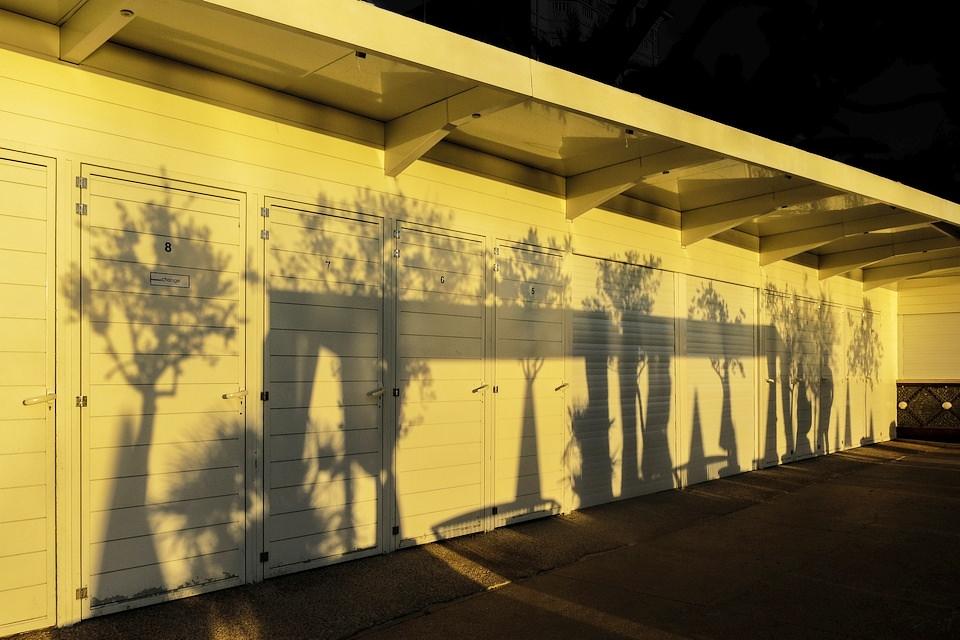 Schatten von Bäumen auf einer Garagenfront.