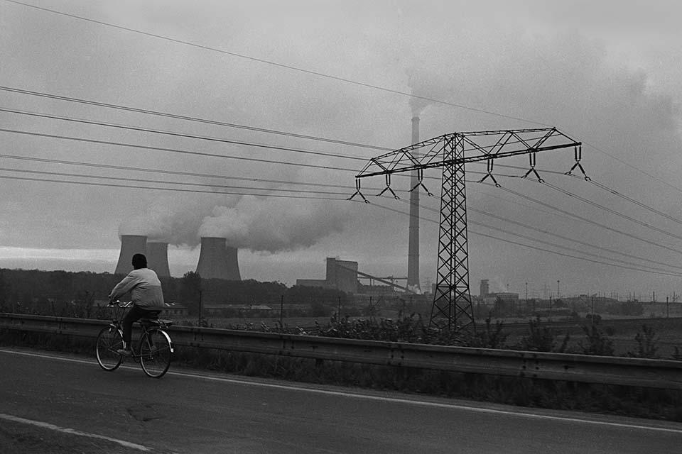 Ein Kohlekraftwerk stößt dicke Rauchschwaden in den bewölkten Himmel aus. Im Vordergrund ein Radfahrer.