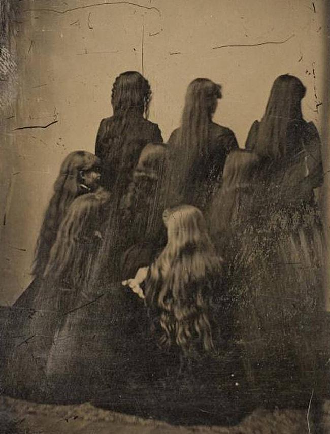 Frauen sitzen vor einer Wand.