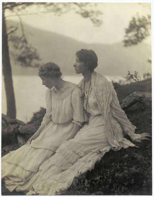 Zwei Frauen sitzen am See.