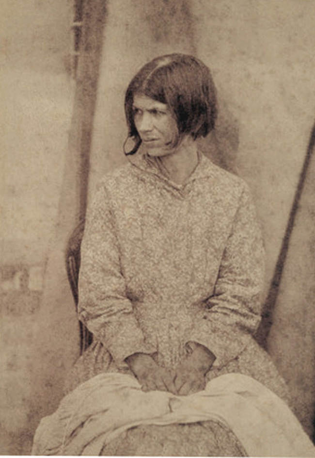 Eine Frau sitzt vor einem Vorhang.