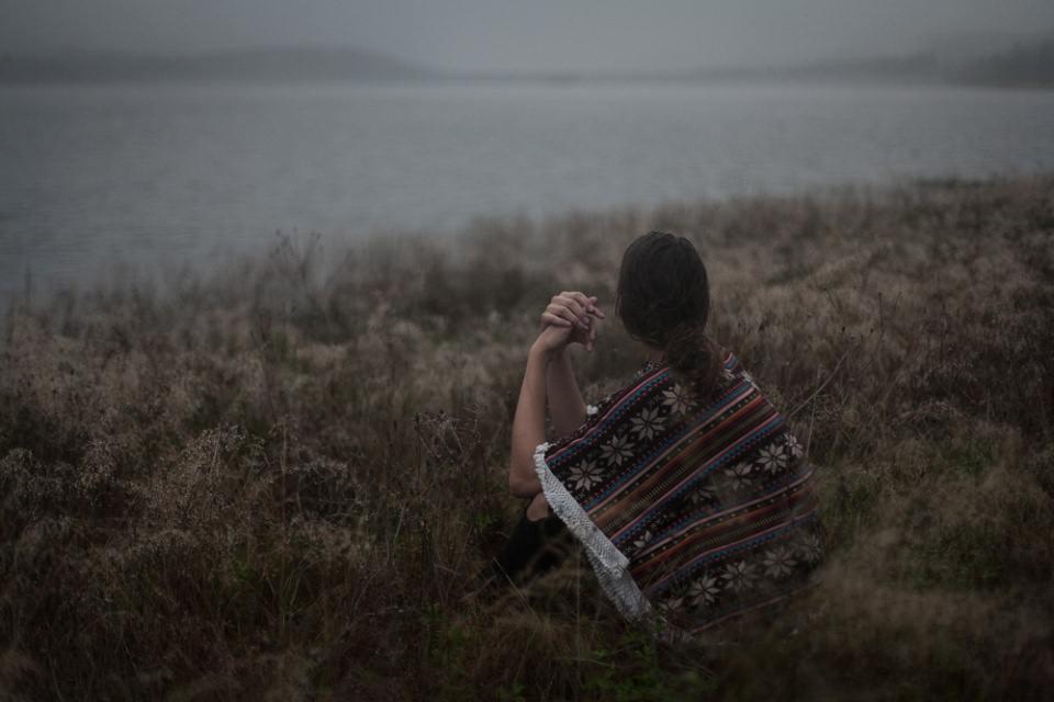 Ein Mädchen mit gemustertem Poncho sitzt auf einer wilden Wiese am Wasser.