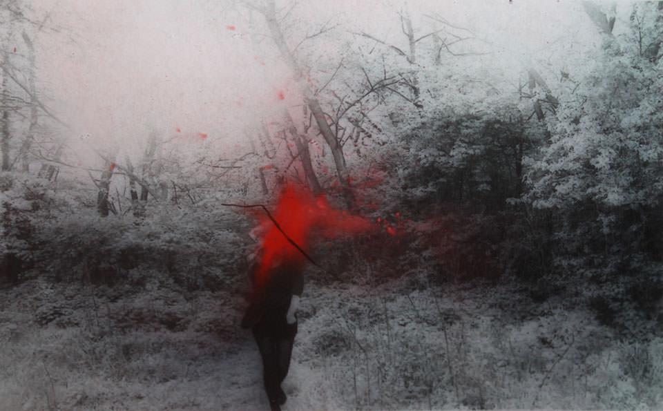 Eine Frau mit roter Farbe im Gesicht steht im Wald.