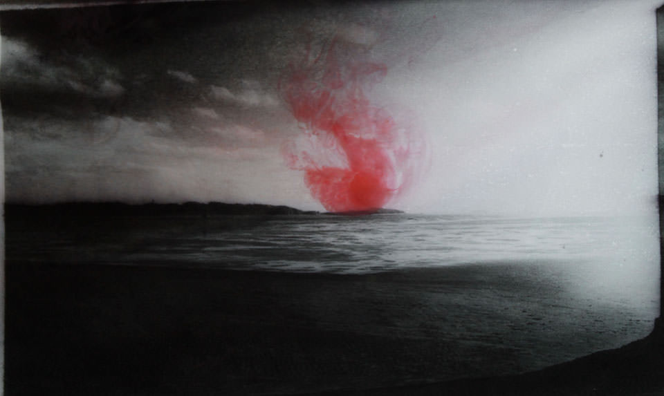 Eine Landschaft in schwarzweiss mit einem roten Fleck.