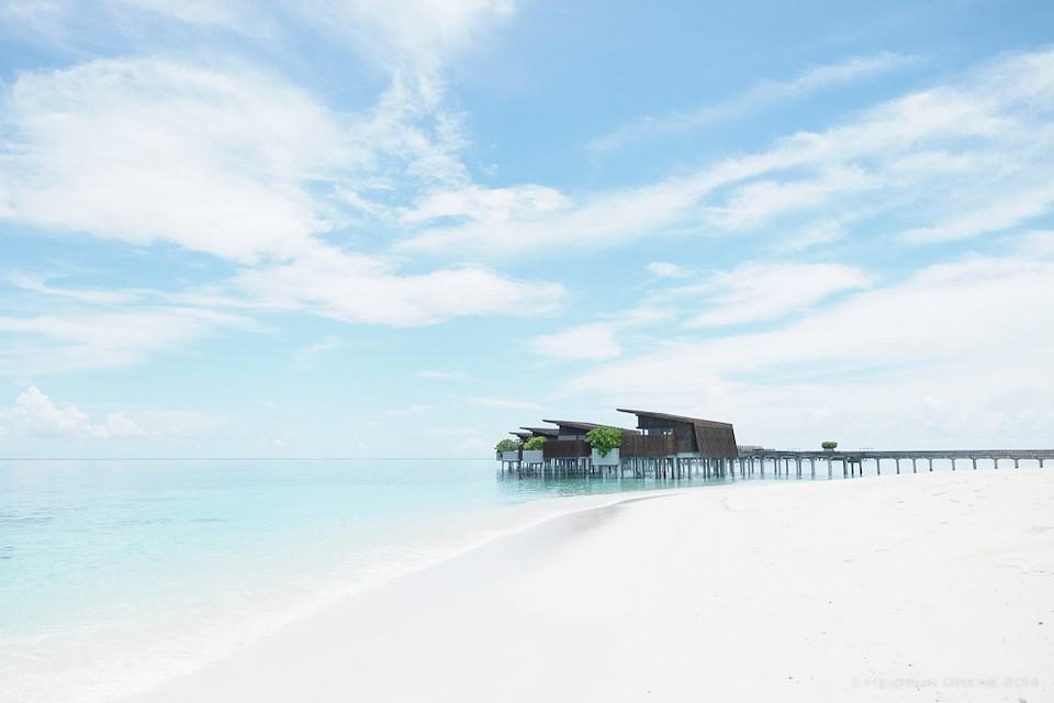 Häuser auf Stelzen an einem weißen Strand unter blauem Himmel.