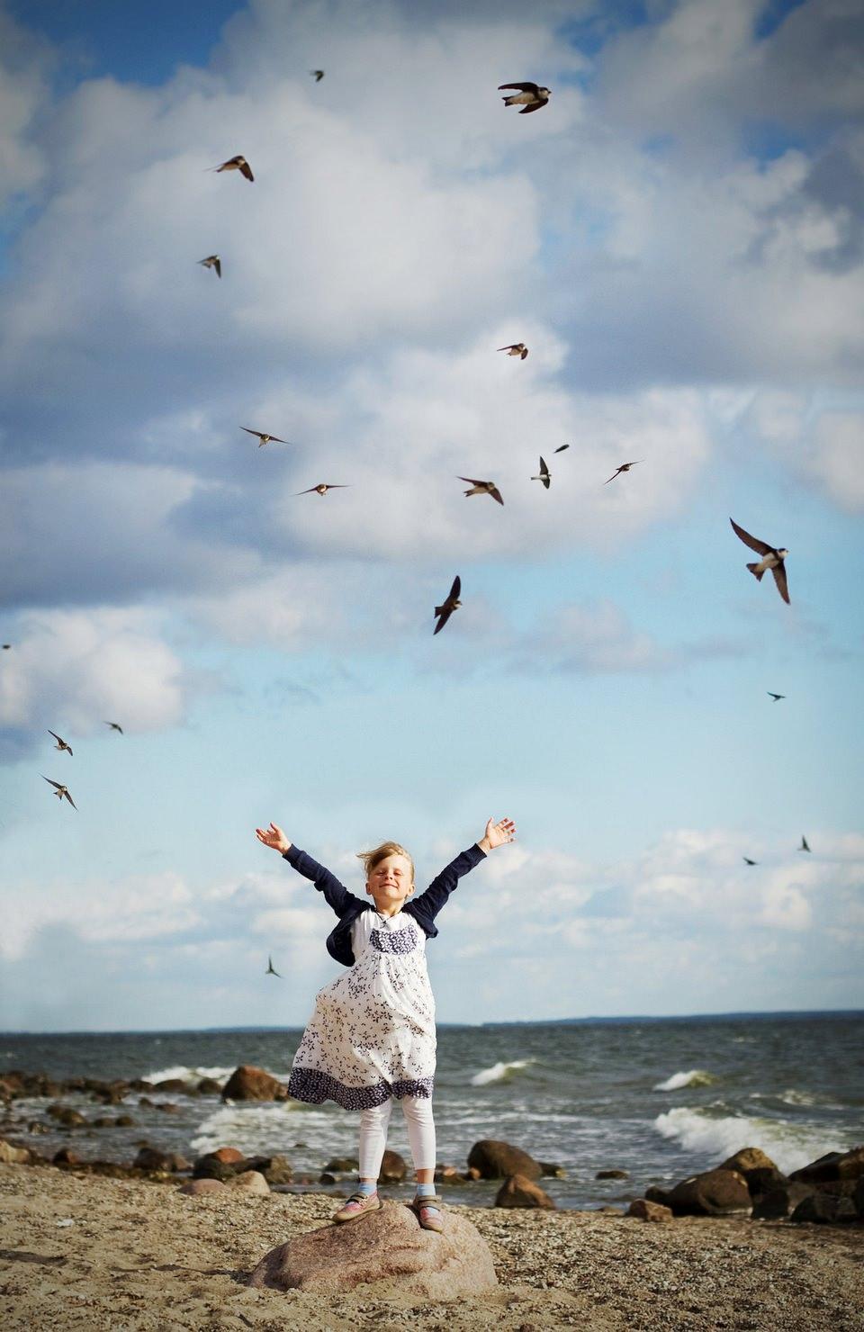 Ein Mädchen steht am Strand und streckt die Arme in die Höhe, darüber fliegen Vögel.