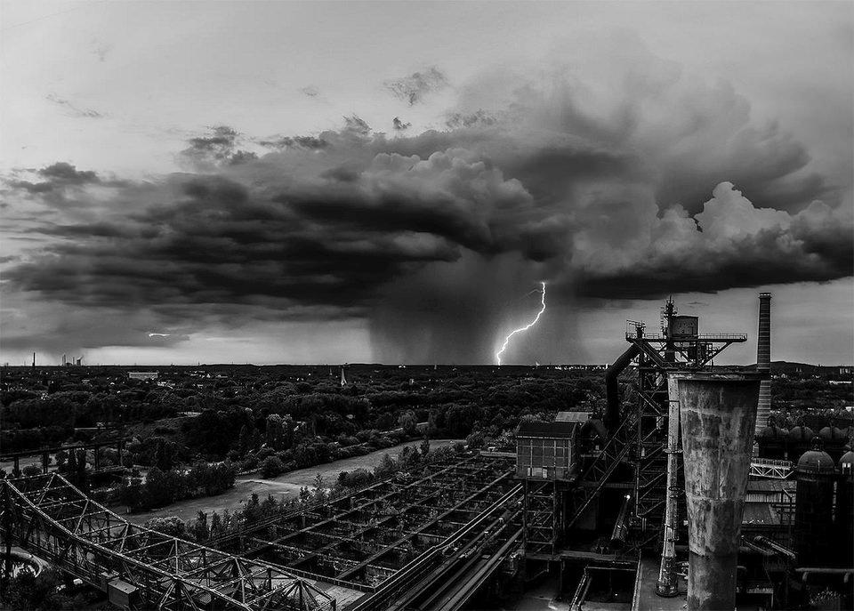 Ein Wolkenbruch mit Blitz über einer Stadt.