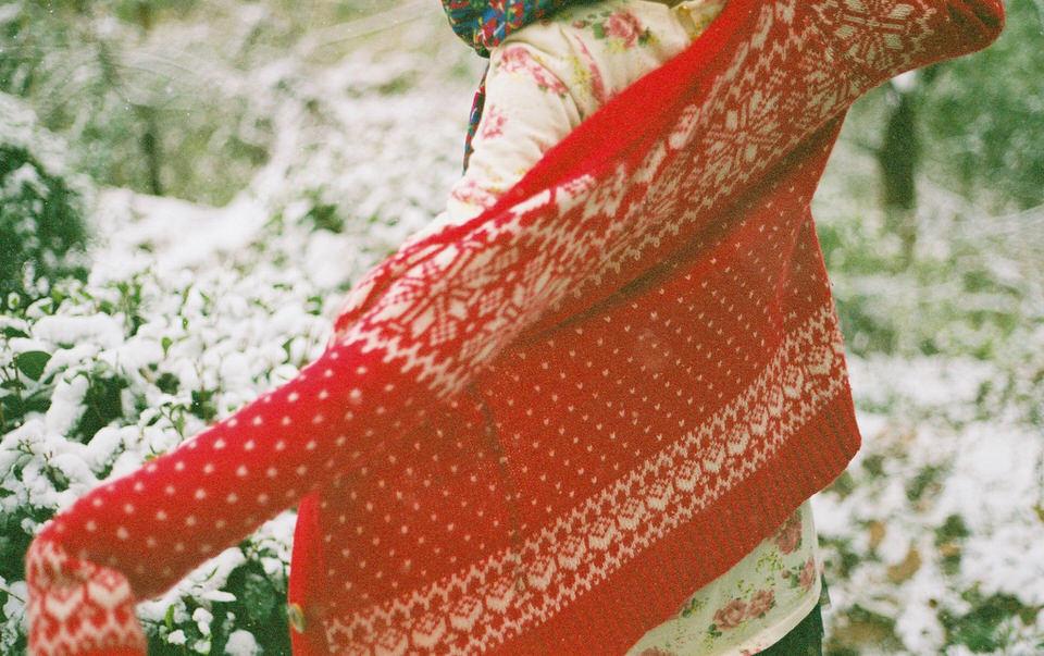 Eine Person zieht eine rote Strickjacke an.