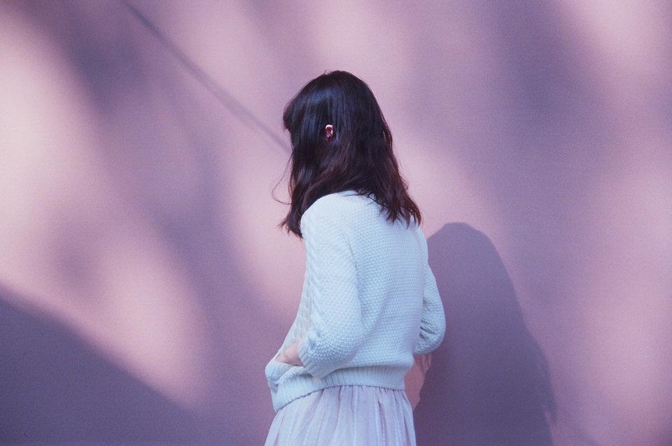 Eine Frau steht vor einer Wand und schaut weg von der Kamera.