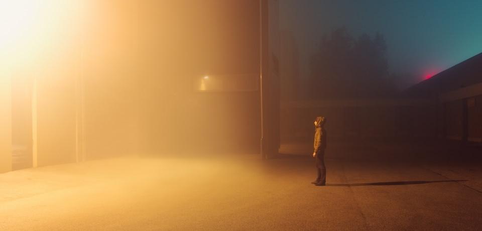 Mensch in nebligem Licht bei Nacht.