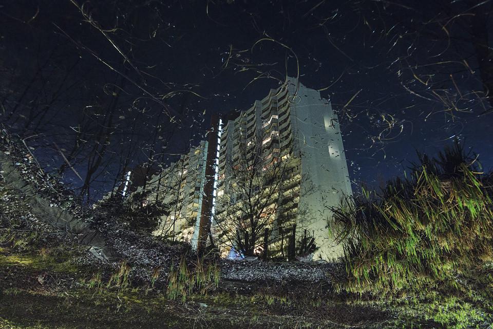 Spiegelung eines Häuserblocks in einer Pfütze bei Nacht.
