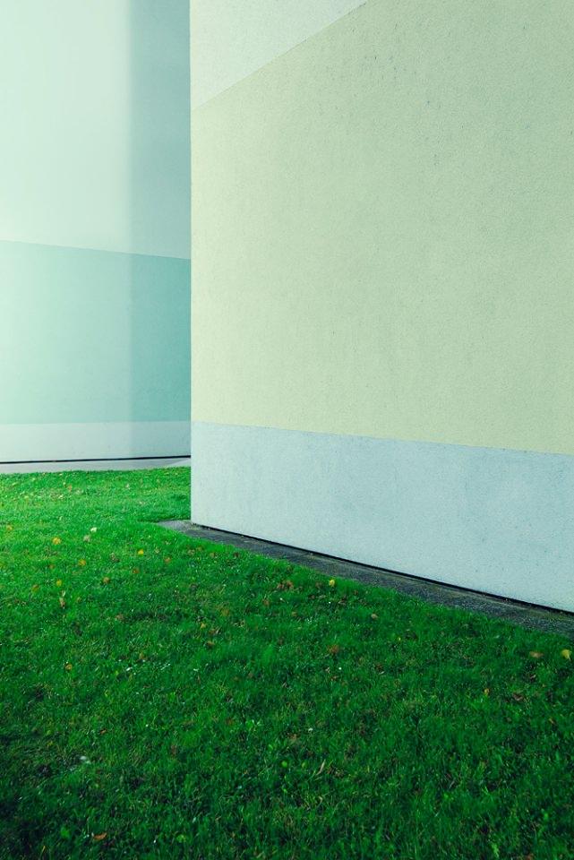 Hausecke, umgeben von grüner Wiese.