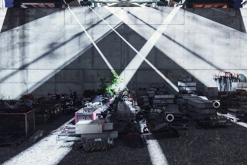 Auf unter einer Überführung abgestellte Bahnutensilien fallen diagonale Lichtstrahlen.