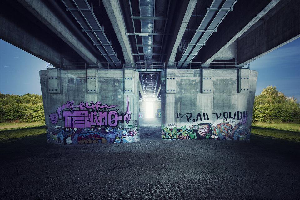 Hell erleuchteter Durchgang unter einer Brücke mit Graffiti.