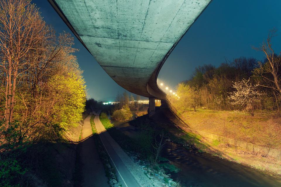 Eine Fahrbahn aus Beton verläuft durch Natur.