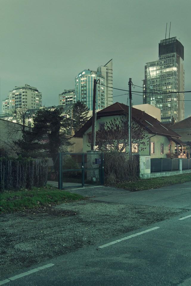 Wohnhaus vor Hochhäusern.