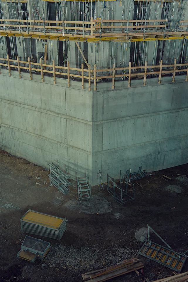 Baugrube mit Betonfundament und Metallgerüsten.