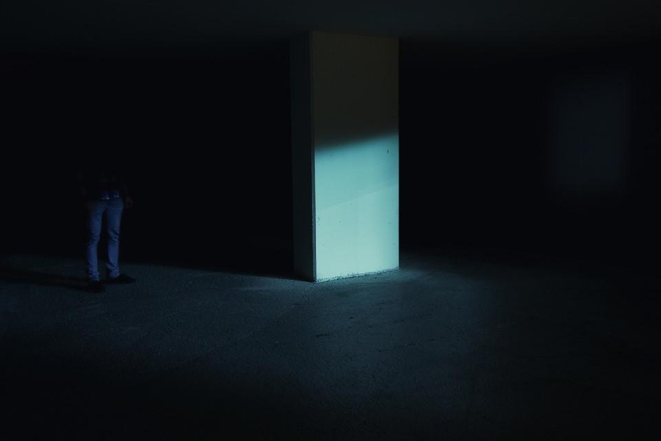 Im Dunkeln nur leicht beleuchtete Beine einer Person neben einem Betonpfeiler.