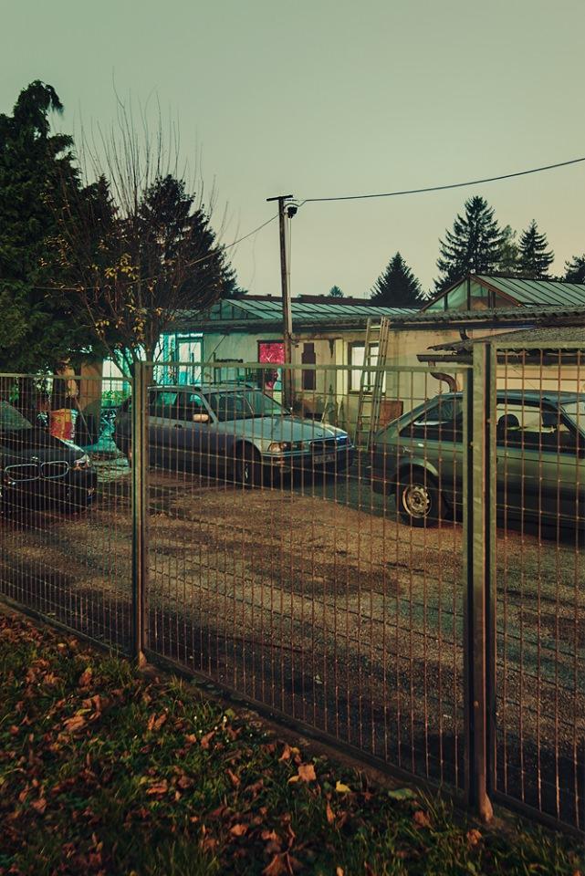 Autos hinter einem Zaun.