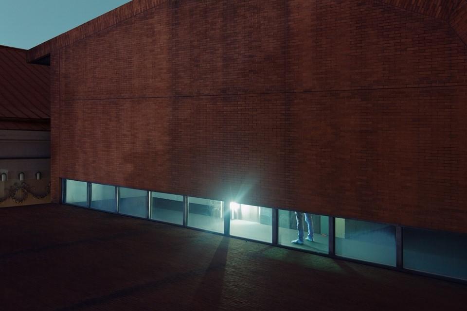 Beleuchtete Beine einer Person, sichtbar durch Bodenfenster in einer Hausfassade.