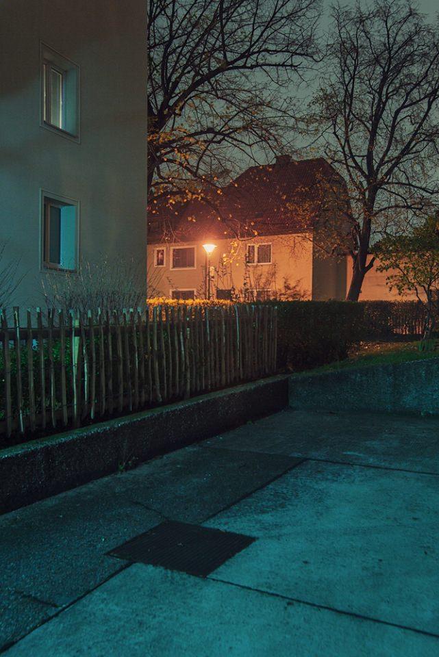 Rot beleuchtetes Haus in blauer Umgebung bei Nacht.