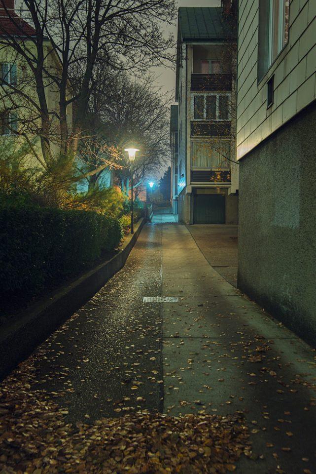 Gasse zwischen Wohnhäusern mit blauem Licht bei Nacht.