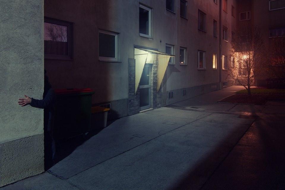 Ein Arm greift um die Ecke eines Wohnhauses, dessen Eingänge blau und rot beleuchtet sind.