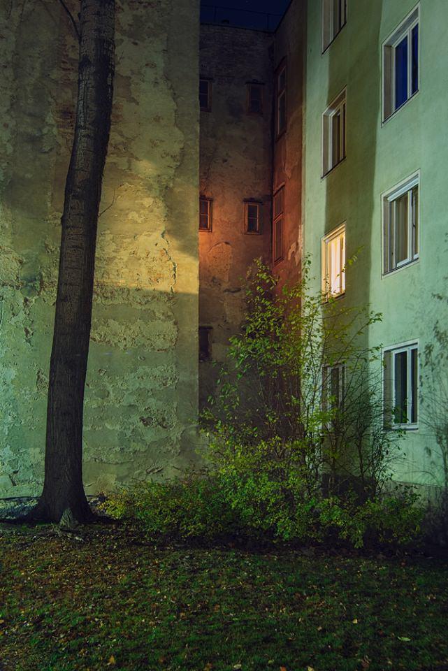 Nische in einer Hausfassade, vor der ein Baum und Büsche stehen.