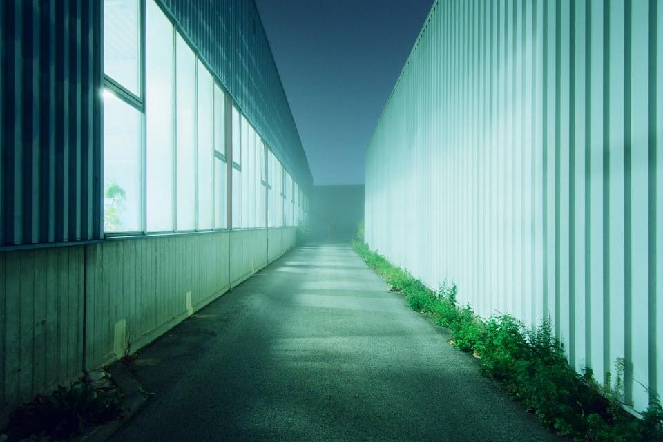 Am Ende eines nebligen, blau beleuchteten Ganges zwischen zwei Containergebäuden steht eine Person.