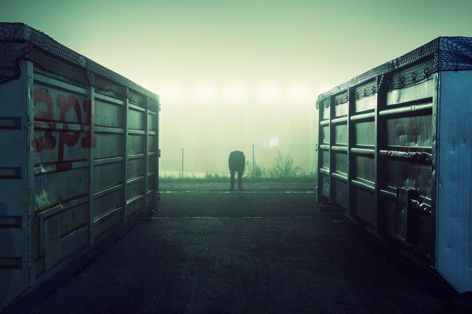 Eine Person steht im nächtlichen Nebel zwischen zwei Metallcontainern.