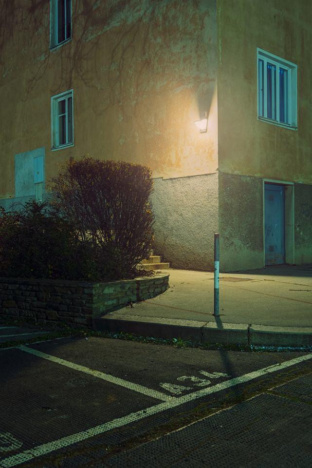 Beleuchtete Hausecke bei Nacht.