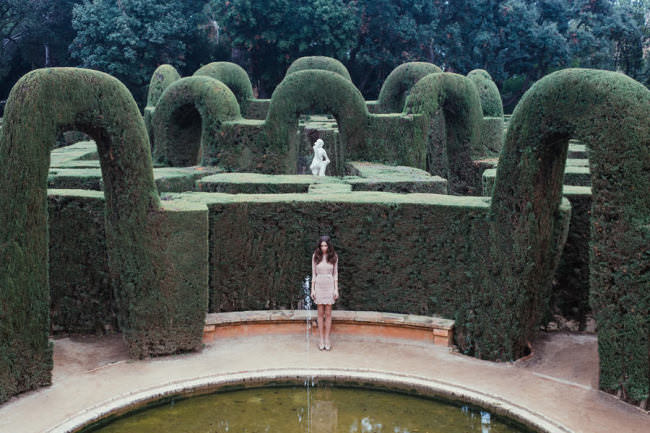 Eine Frau vor einem Heckenlabyrinth.