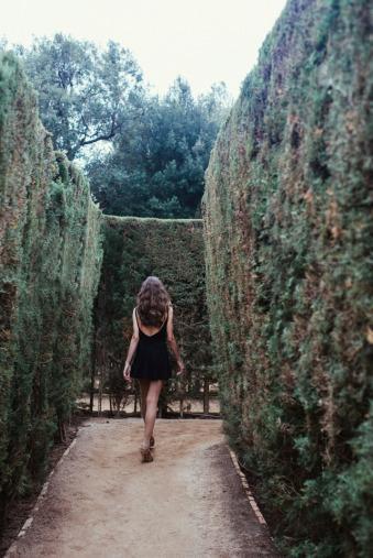Eine Frau läuft in ein Heckenlabyrinth.
