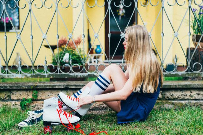Eine Frau sitzt im Vorgarten und bindet sich Rollschuhe zu.