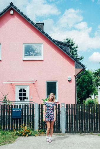 Eine Frau im Sommerkleid steht vor einem Haus mit Vorgarten.