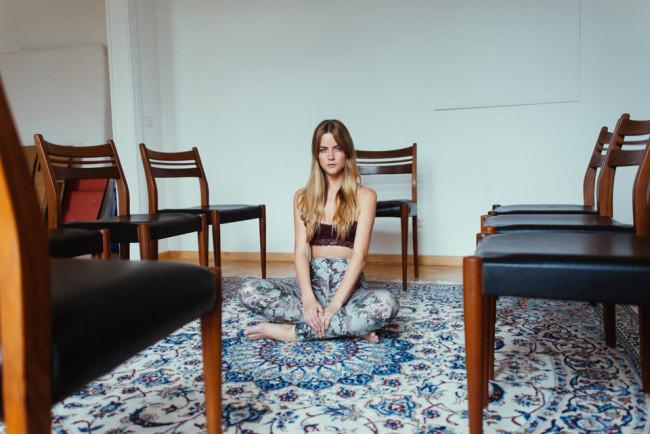 Eine Frau sitzt auf einem Teppich in einem leeren Stuhlkreis.