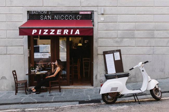 Eine Frau sitzt vor einer Pizzeria neben einem Moped.